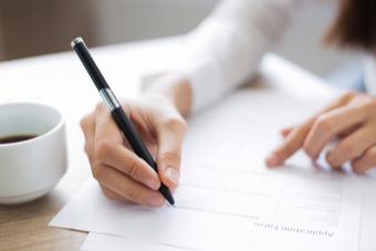 Frau mit Stift in der Händ schreibt Bewerbung - Studilux