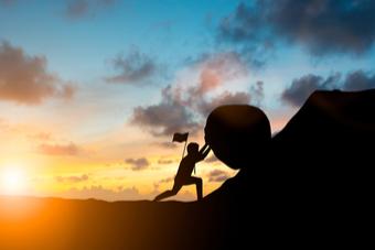 Mann rollt Stein auf Berg als Sinnbild für Motivation - Studilux