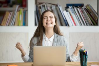 Frau sitzt vor Laptop und freut sich - Studilux
